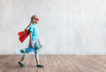 Little super girl with a skateboard