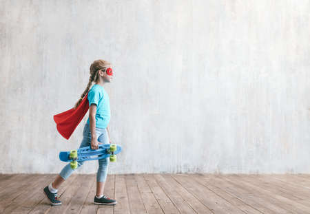 Little girl with a skateboard in studio