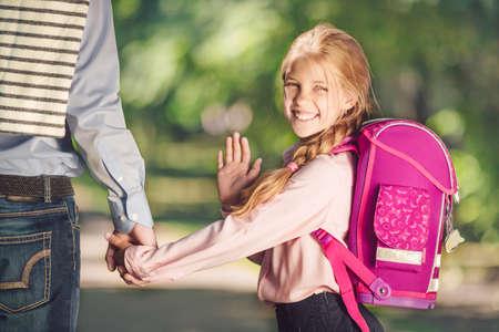 Lächelndes Schulmädchen mit Rucksack Standard-Bild