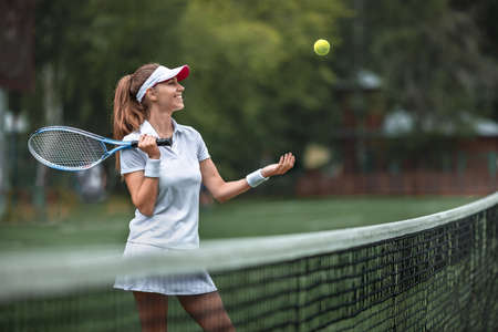 Smiling woman with a racket and tennis ball on the court