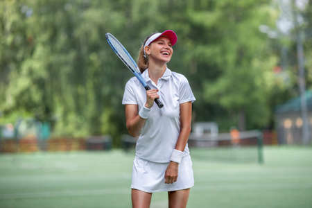 Happy young woman on the tennis court