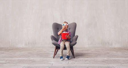 Little child in 3d glasses eating popcorn indoors 스톡 콘텐츠