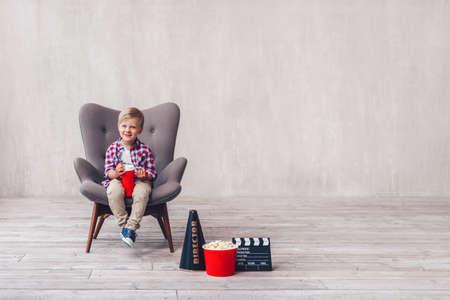 Niño sonriente con palomitas de maíz en el cine