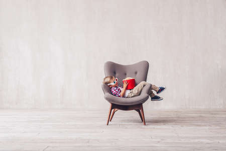 Sleeping little child with popcorn in a cinema chair Stock Photo