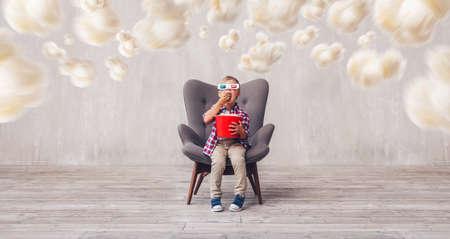 Little child in 3d glasses eating popcorn in studio