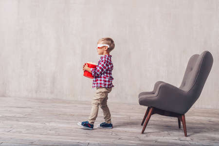 Little child in 3d glasses with popcorn at home 스톡 콘텐츠