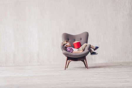 Sleeping little boy with popcorn in a cinema chair