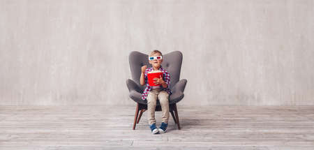 Little boy in 3d glasses with popcorn in cinema