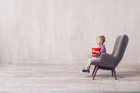 Smiling boy with popcorn and a remote control at home