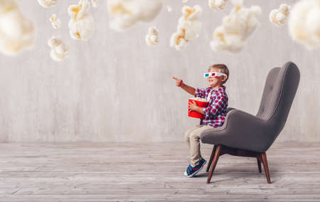 Happy child with popcorn in a cinema chair