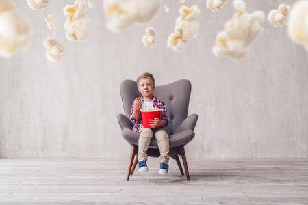 Little boy eating popcorn in a cinema chair