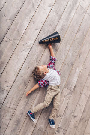 Little boy with a megaphone on the wooden floor
