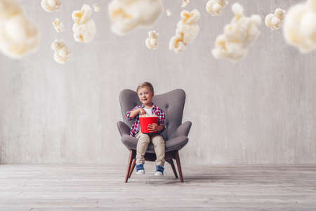Smiling child eating popcorn in a cinema chair