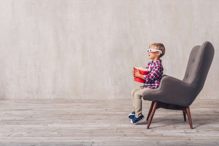Little child in 3d glasses with popcorn in a chair