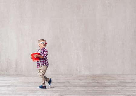 Little child in 3d glasses with popcorn in studio