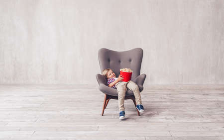 Smiling child with popcorn in a chair