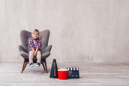Little kid in a chair at home 스톡 콘텐츠
