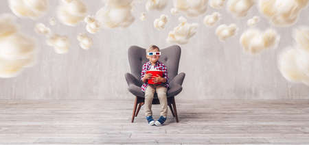 Smiling kid with popcorn in 3d glasses at home