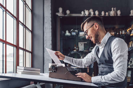 Smiling professional with retro typewriter at the window Stock Photo