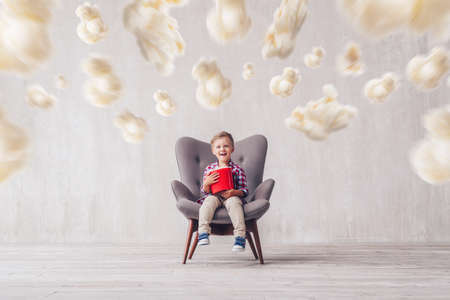 Smiling little spectator with popcorn at home Archivio Fotografico - 112655400
