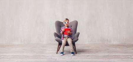 Little kid with popcorn in 3d glasses at home