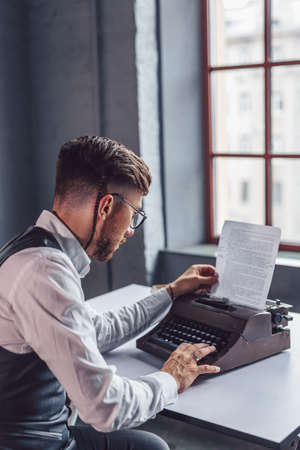 Working man with a retro typewriter in the office Stock Photo
