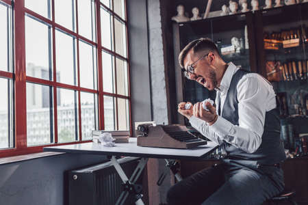 Angry man with retro typewriter in the office Stock Photo