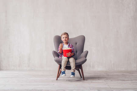 Little kid with popcorn at home