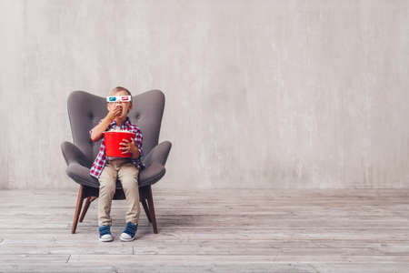 Little kid with popcorn at home Archivio Fotografico - 112592733