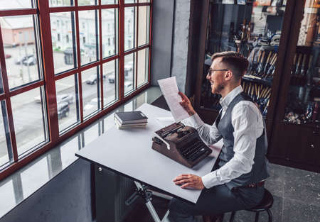 Smiling writer with retro typewriter in the office Stock Photo