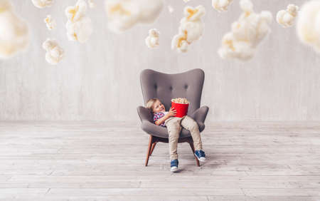 Smiling little boy with popcorn at home 스톡 콘텐츠
