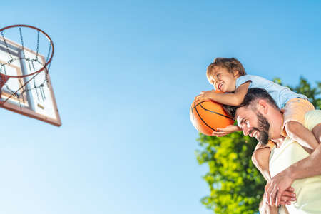 Father and son playing basketball in summer
