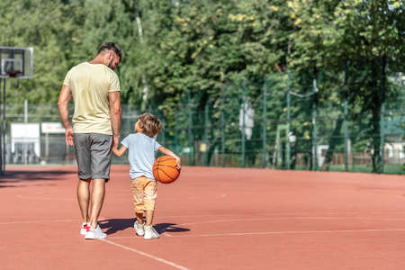 Father and son on the basketball court in summer