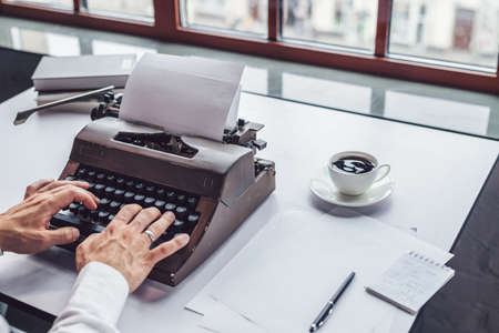Mens hands typing on a retro typewriter close-up Stock Photo