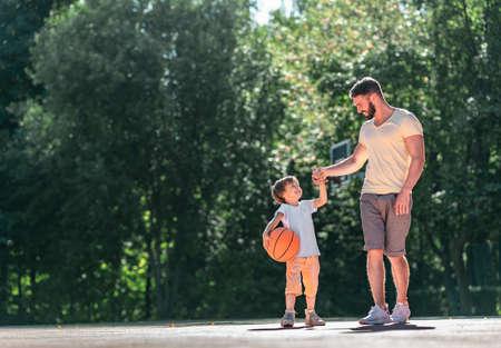 Padre e hijo con una pelota en la cancha de baloncesto