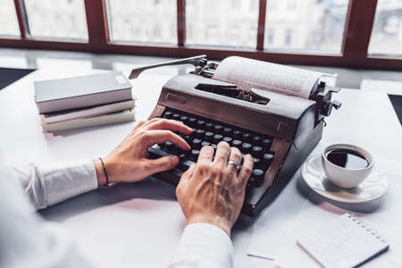 Young writer typing on a retro typewriter close-up Stock Photo