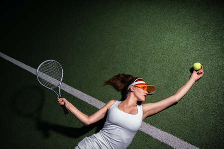 Attractive girl playing tennis on a court Stok Fotoğraf