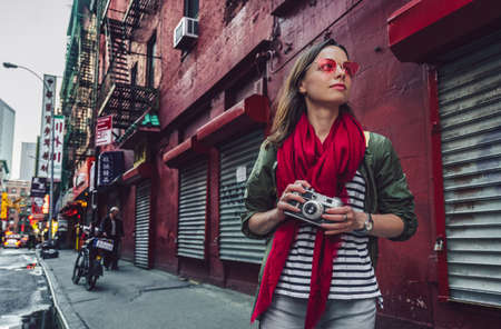 Attractive girl with a retro camera in Chinatown in New York