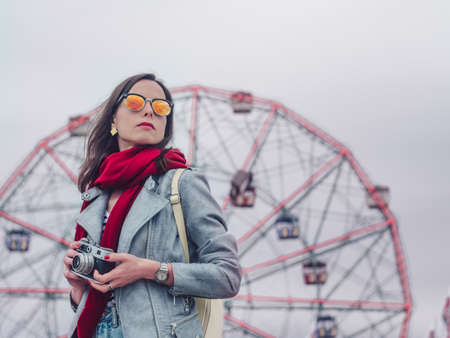 Young girl with retro camera on background of the ferris wheel Stock Photo