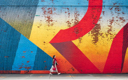 Young girl walking by the wall with graffiti in New York