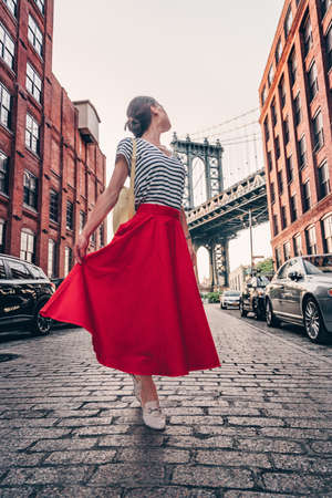 Beautiful girl in a red skirt on the background of the Manhattan bridge