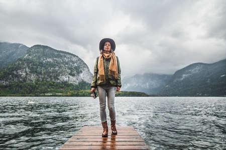 Young traveler with a retro camera in Hallstatt in Austria