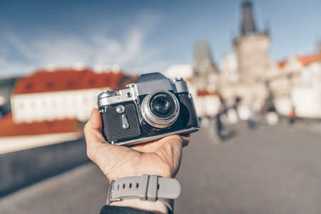 Male hand with a camera on the background of Prague