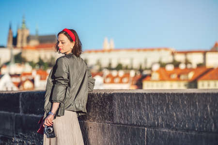 Attractive girl with retro camera on the bridge in Prague