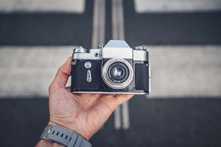 Mens hands with a retro camera on the background