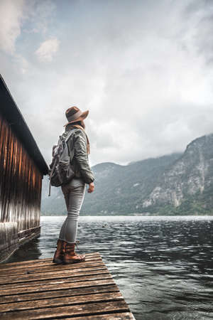 Young woman with a backpack on a pier by the lake Stock Photo