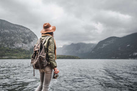 Young woman in a hat by the lake