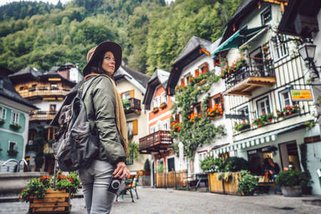 Beautiful young girl with a retro camera in Hallstatt