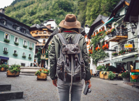 Young woman with a retro camera in an alpine village