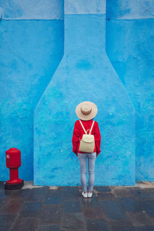 Young girl with a backpack on a background of blue wall Stock Photo